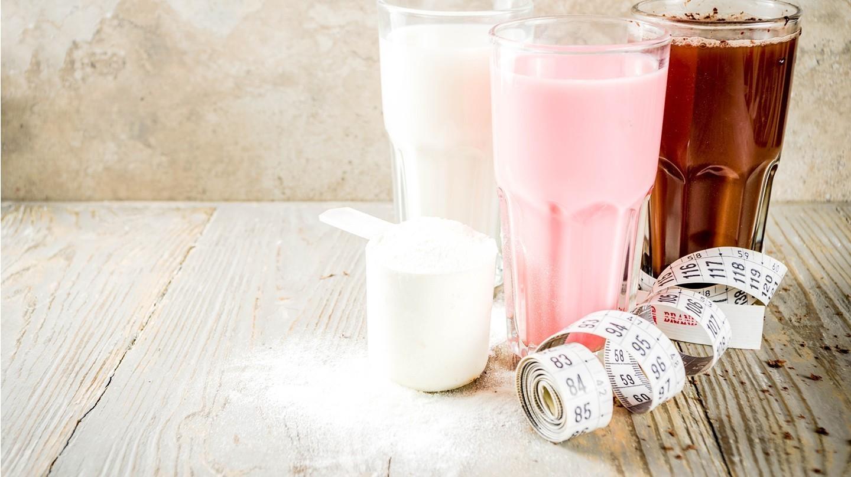 Bakterien im Darm: Drei Gläser mit Shakes zum Abnehmen, ein Messlöffel mit Pulver und ein Maßband.