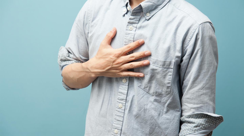 Sodbrennen: Ein Mann in graublauem Hemd legt die Hand auf die Brust.